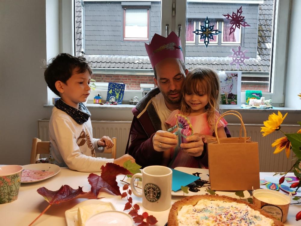 Linus, Elin und Daniel sitzen am Frühstückstisch, Daniel trägt weine mit glitzer verzierte Pappkrone